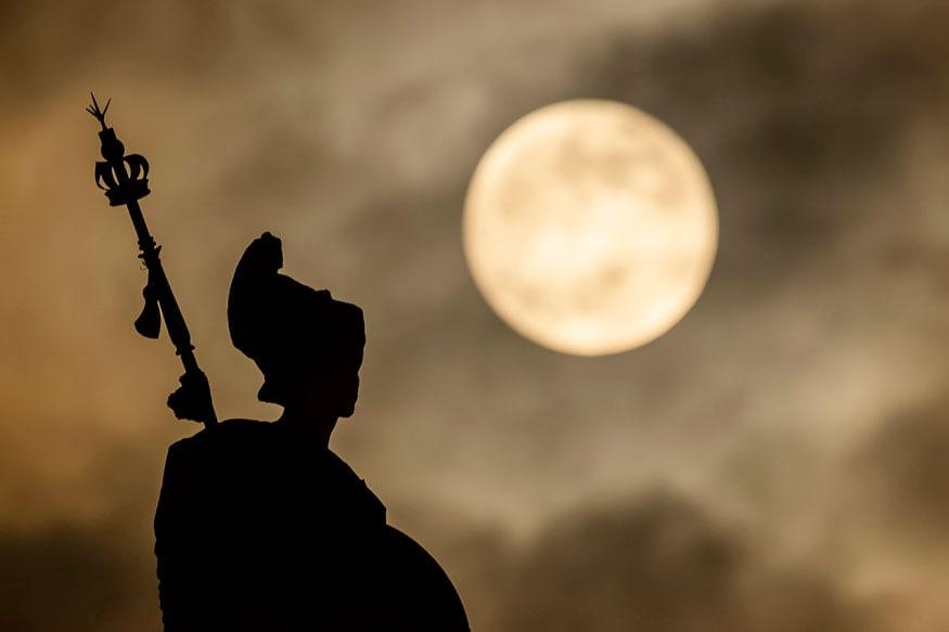 इंग्लैंड के हल में चंद्रग्रहण से पहले हल गुइल्डहॉल में ब्रिटानिया की मूर्ति के ऊपर कुछ इस तरह दिखा सुपर ब्लड वुल्फ मून. (छवि: एपी)