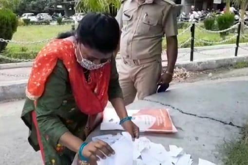चिथड़े-चिथड़े हो गई अपनी फ़ाइल को संभालती महिला.