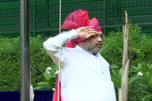 दिल्ली स्थित आवास पर ध्वजारोहण के बाद झंडे को सलामी देते गृह मंत्री अमित शाह
