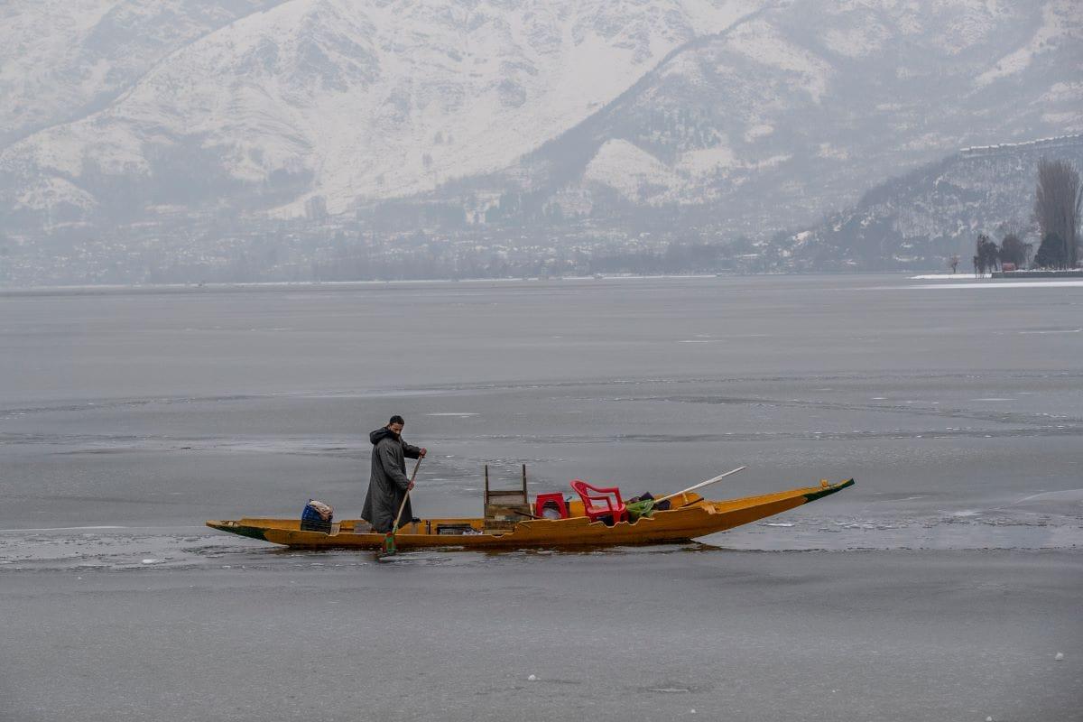 बर्फबारी के कारण जम्मू कश्मीर में ठंड बेहद बढ़ गई है. इससे डल झील पूरी तरह से जम गई है. अब इसमें शिकारे भी नहीं चल रहे. (Pic- AP)
