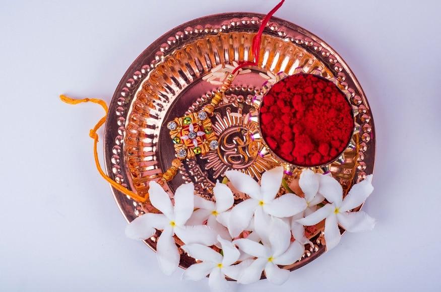 रक्षा बंधन के दिन पूजा की थाली पर गंगा जल छिड़क कर उसमें कुमकुम या रोली रखें. इसी कुमकुम से बहनें भाई का तिलक करती हैं. (Image-Shutterstock)