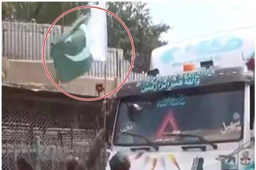 पाकिस्तान का झंडा उतरवाते तालिबान लड़ाके  (Twitter)