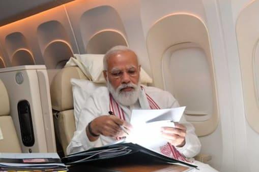 फ्लाइट में फाइलें देखते PM नरेंद्र मोदी. (PIC: Twitter)