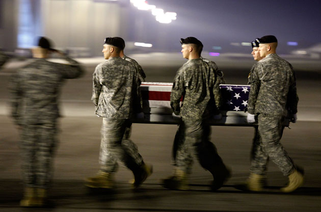 Members of a US Army carry team move the transfer case of US Army Sergeant Aaron M Smith during a dignified transfer at Dover Air Force Base on October 3, 2009 in Dover, Delaware. Sergeant Aaron M Smith who was from Manhattan, Kansas was killed in Afghanistan while supporting Operation Enduring Freedom.