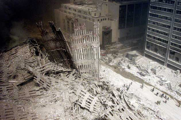 A group of firefighters walk amid rubble near the base of the destroyed south tower of the World Trade Center in New York in this file photo from September 11, 2001. This year's anniversary of the September 11 attacks in New York and Washington will echo the first one, with silence for the moments the planes struck and when the buildings fell, and the reading of 2,792 victims' names.