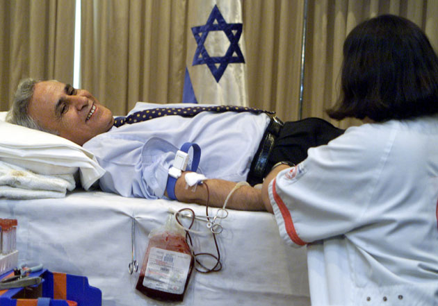 Israeli President Moshe Katsav donates blood in his Jerusalem residence September 12, 2001, for the victims of yesterday's terrorist attacks in the United States. Israel has declared a national day of mourning in solidarity with the US after devastating aircraft attacks in New York and Washington DC Flags flew at half-mast across the Jewish state as Israel expressed its sorrow over the unprecedented assault on its main ally while scores of Israelis and others donated blood.
