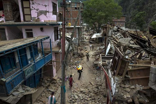 Local residents walk past collapsed buildings after Tuesday's earthquake at Singati Village, in Dolakha, Nepal. (Reuters)
