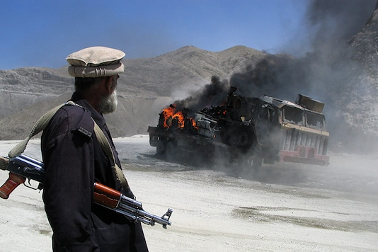 File photo of a Pakistani security official stands near a burning vehicle after it was attacked in Chaman in Pakistan's Balochistan province, along the Afghan border. (File Photo: Reuters/Saeed Ali Achakzai)
