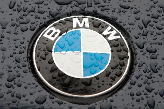 The logo of German car manufacturer BMW is seen on the bonnet of a vehicle covered with water drops. (REUTERS)