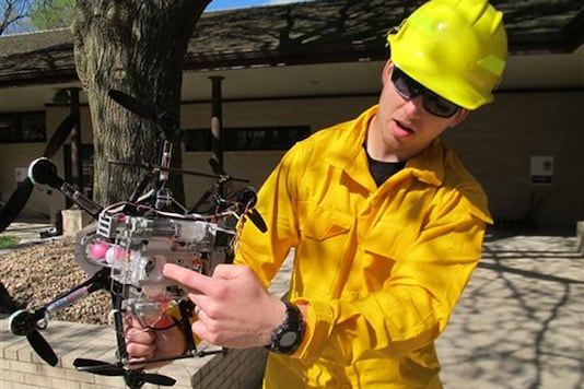 University of Nebraska-Lincoln graduate student Jim Higgins displays the drone he helped create before its flight at the Homestead National Monument of America in Beatrice, Neb., on Friday, April 22, 2016. The drone drops ping-pong-sized balls intended to start brush-clearing grass fires. (AP Photo/Grant Schulte)