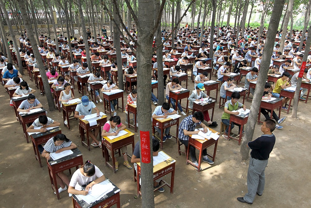 Students take term final exam among trees outside a classroom building at a middle school in Xinxiang, Henan province, China, July 3, 2015. The school set up the exam outdoor to create a more comfortable environment for the students, according to local media. Picture taken July 3, 2015. REUTERS/Stringer CHINA OUT. NO COMMERCIAL OR EDITORIAL SALES IN CHINA. - RTX1IYUV
