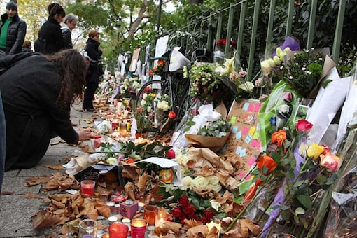People lay flowers and light candles at a makeshift memorial for the victims of the Paris terror attacks. (Getty Images)