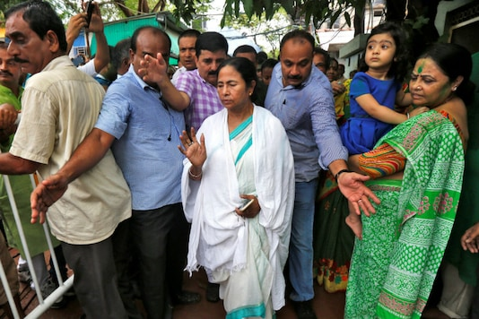 TMC chief Mamata Banerjee (C) waves towards her supporters outside her residence after the initial poll results of the West Bengal Assembly elections.
