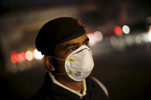 A traffic policeman wears a mask to protect himself from dust and air pollution as he stands on a road divider in New Delhi.