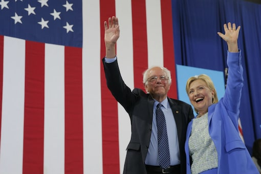 Hillary Clinton and Bernie Sanders stand together during a campaign rally where Sanders endorsed Clinton in Portsmouth, New Hampshire (Reuters)