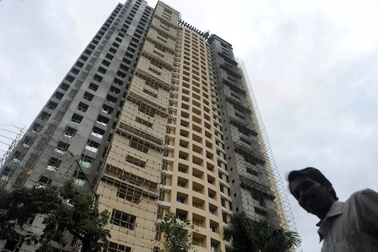 A local resident walks past the controversial Adarsh Housing Society apartments in Mumbai. (AFP)