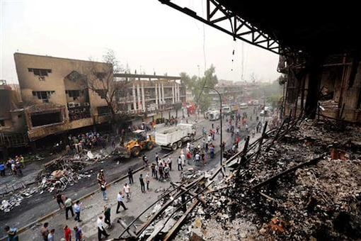 Iraqi security forces and civilians gather at the site after a car bomb hit Karada, a busy shopping district in Baghdad. (AP)