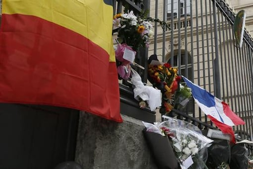 A Belgian flag is displayed next to flowers and candles in front of the Belgium embassy in Paris, France, March 23, 2016 in tribute to the victims of Tuesday's bomb attacks in Brussels.