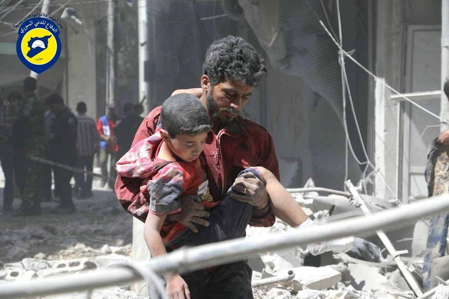 (Photo: AP/Syrian man carries an injured boy, in Aleppo, Syria.)
