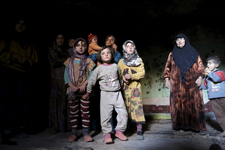 Internally displaced Syrians stand inside their makeshift shelter that is an underground cave in Om al-Seer, southern Idlib countryside, Syria