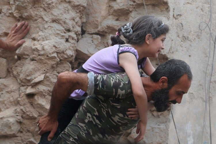 A man carries an injured girl after an airstrike on Aleppo's rebel held Kadi Askar area