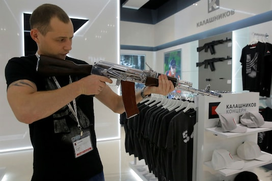 A salesperson demonstrates a model AK-47 assault rifle at the newly opened Gunmaker Kalashnikov souvenir store in Moscow's Sheremetyevo airport, Russia. (Reuters)