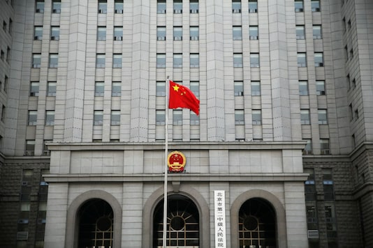 File photo: A Chinese national flag flutters in front of a building.