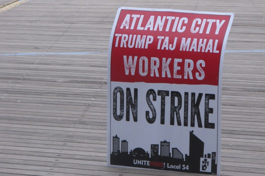(Photo: AP/A striker's sign is displayed on the Boardwalk in Atlantic City.)