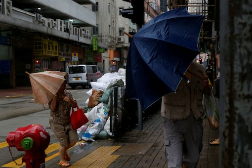 People brave strong winds on a street as Typhoon Haima approaches in Hong Kong, China, October 21, 2016/REUTERS