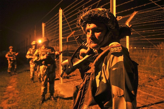 Border Security Force (BSF) soldiers standing guard during a night patrol near the fence at the India-Pakistan International Border at the outpost of Akhnoor sector on October 3, 2016 about 40 km from Jammu.  (Photo Credit: Getty Images)