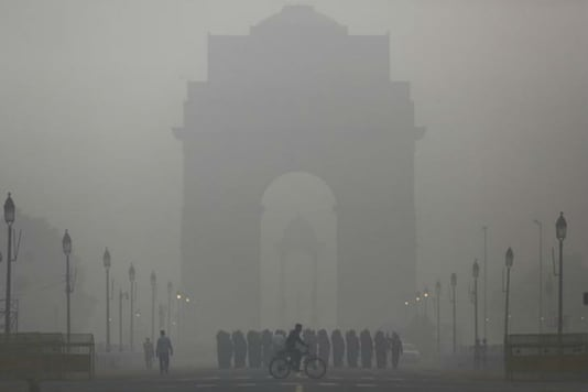 In this file photo,  a man rides his bicycle next to Army Jawans marching in front of India Gate on a smoggy morning in New Delhi.