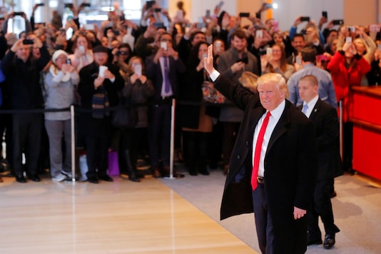US President-elect Donald Trump reacts to a crowd gathered in the lobby of the New York Times building after a meeting in New York. (Reuters)