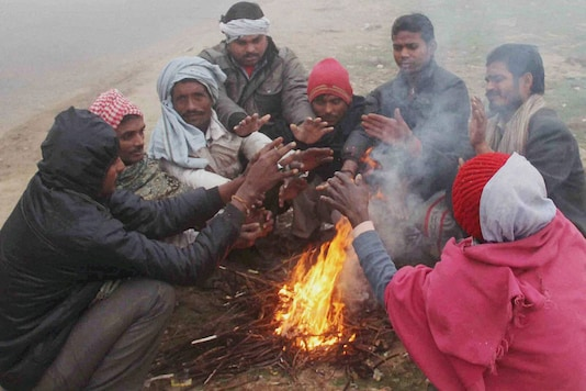 People sit around a bonfire to warm themselves on a cold and foggy morning (Photo: PTI)