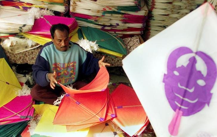 Indian kitemaker puts the final touches on his kites in Amritsar.
