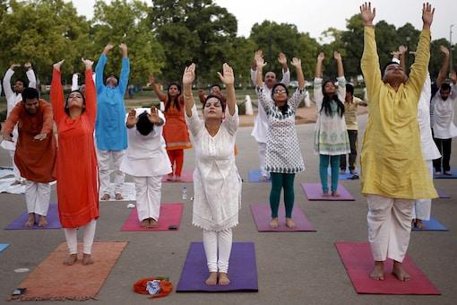 "Participants perform a ""Surya Namaskar"" (sun salutation) during an early morning yoga session  (Reuters)"