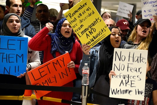 Dozens of pro-immigration demonstrators cheer and hold signs as international passengers arrive at Dulles International Airport, to protest President Donald Trump's executive order barring visitors, refugees and immigrants from certain countries to the United States, in Chantilly, Virginia, in suburban Washington, U.S (Reuters)