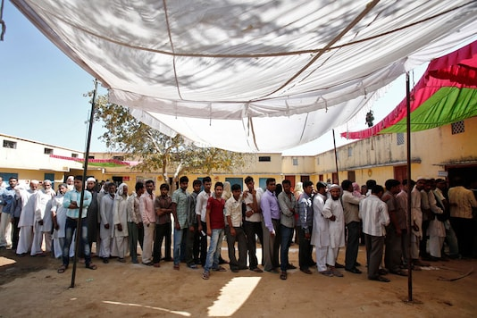 File photo of men stand in a line to cast their vote outside a polling station (REUTERS)