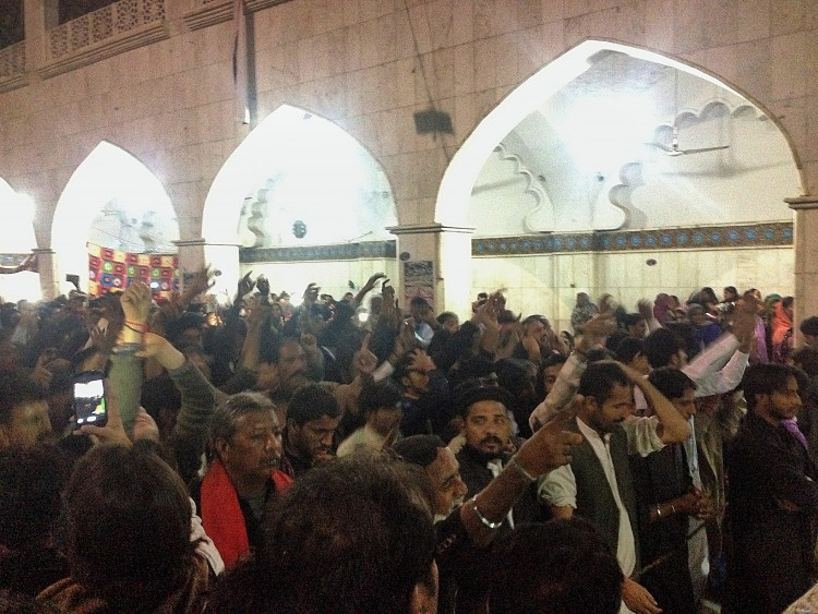 Worshippers during dhamaal reaching out for the sky, asking for Shahbaz Qalandar's blessings and chanting Hazrat Ali's name in remembrance.