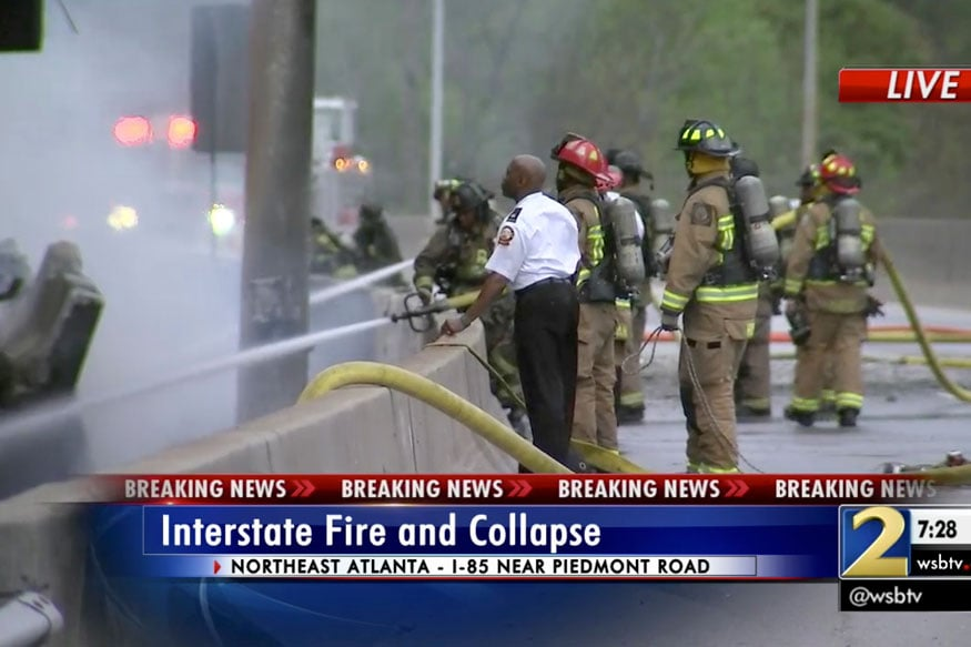 Firefighters douse a blaze after the large fire caused an overpass on Interstate 85 to collapse in Atlanta (WSB-TV via AP)