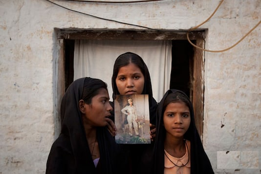The daughters of Pakistani Christian woman Asia Bibi pose with an image of their mother while standing outside their residence in Sheikhupura located in Pakistan's Punjab Province. Standing left to right is Esha, 12, Sidra, 18 and Eshum, 10. (Image: Reuters)