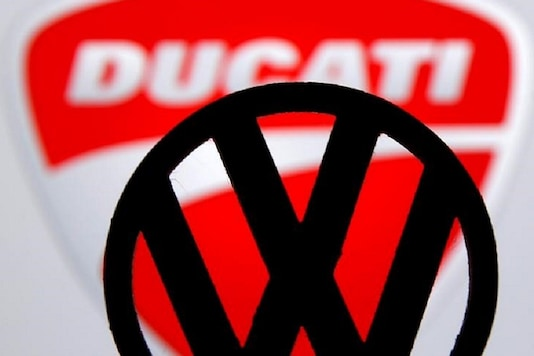 A 3D printed Volkswagen logo is seen in front of a displayed Ducati logo. (Image: Reuters)