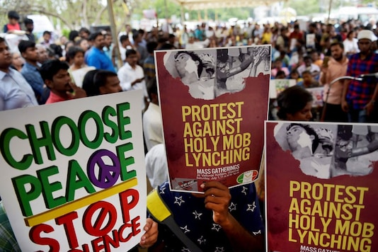 File photo of people hold placards as they participate in a protest against targeted lynching. (Image: PTI)