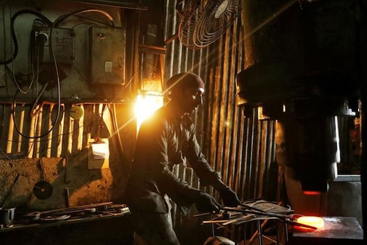 A worker operates a hydraulic press machine at a workshop manufacturing flanges for automobiles in Mumbai. Image: Reuters