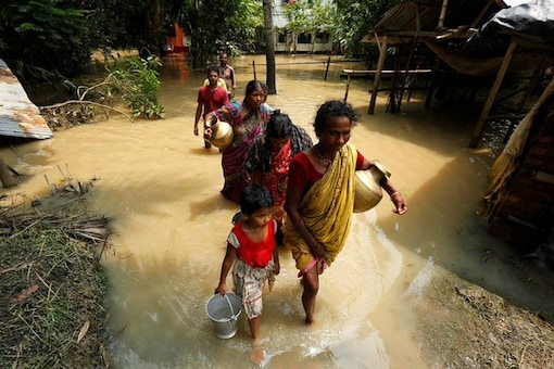 People wade through a flooded road to collect drinking water in Howrah district, West Bengal. (File photo/Reuters)