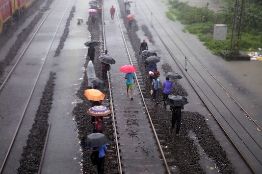People walk on water-logged railway tracks during rains at a railway station in Mumbai, India, August 29, 2017. (Photo: Reuters/Shailesh Andrade)