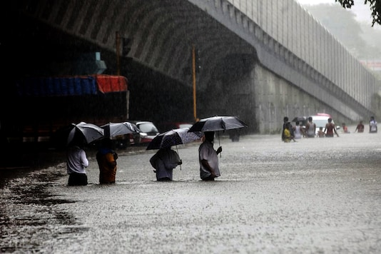 People wade along a flooded street during heavy rain in Mumbai. (Getty Images)