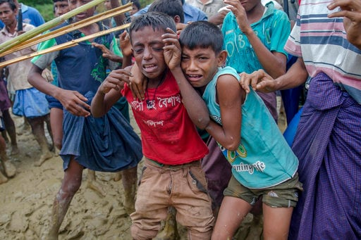 FILE - In this Wednesday, Sept. 20, 2017, file photo, Rohingya Muslim boys, who crossed over from Myanmar into Bangladesh, cry as Bangladeshi men push them away during the distribution of food aid near Balukhali refugee camp, Bangladesh. Children make up about 60 percent of the sea of humanity that has poured into Bangladesh over the last four weeks fleeing terrible persecution in Myanmar. And the UN's child rights agency UNICEF has so far counted about 1,400 children who have crossed the border without their parents. (AP Photo/Dar Yasin, File)