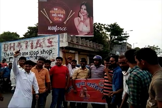 Hindu Yuva Vahini activists protesting in front of the hoarding featuring a condom ad with Sunny Leone.