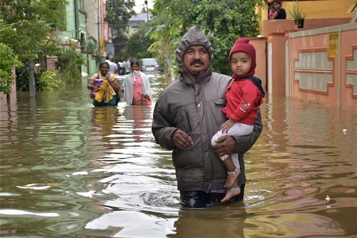 Hyderabad: People wade through a flooded road at East Anand Bagh, Malkajgiri near Hyderabad on Thursday following heavy overnight rains. (Image: PTI)