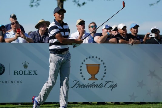 Rickie Fowler watches his tee shot on the ninth hole during the first round foursomes match of The President's Cup golf tournament at Liberty National Golf Course. Kyle Terada-USA TODAY Sports